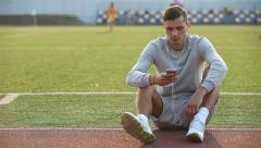 Sportsman sitting on the grass in the stadium and touching his phone Stock Footage