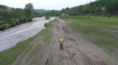A river in a valley and KTM motorcyclist passing by Stock Footage