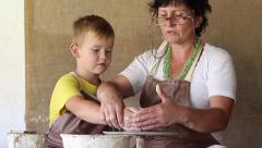 Stock Video Footage of An experienced guide handles the potter young apprentice