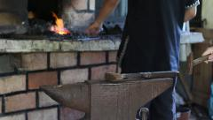 Blacksmith forges a horseshoe then heats it in the oven with coal Stock Footage