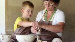 Woman potter's hand directs a small disciple, molding clay products Stock Footage