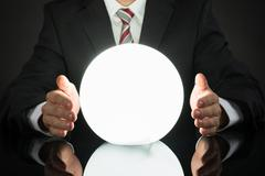 Close-up Of Businessman Predicting Future With Crystal Ball At Desk Stock Photos