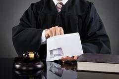 Close-up Of Judge Putting Money In Envelope At Desk In Courtroom - stock photo
