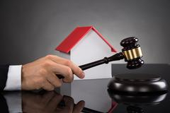 Close-up Of Judge With House Model Hitting Gavel At Desk - stock photo