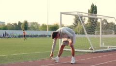 Young athlete doing a warm up leg stretch before a race Stock Footage
