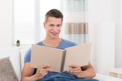 Portrait Of Young Happy Man With Photo Album Sitting On Sofa Stock Photos