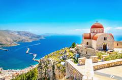 Remote church with red roofing on cliff, Greece Stock Photos