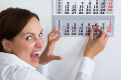 Close-up Of Frightening Businesswoman Marking Friday 13 On Calendar Stock Photos
