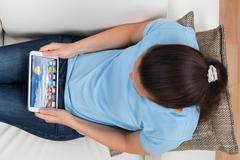 Young Woman Sitting On Sofa With Digital Tablet Showing Apps Stock Photos