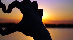 Woman makes heart  hands directs the sunset - stock footage