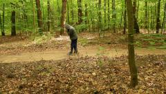 Creepy axeman walking through the forest with an axe - stock footage