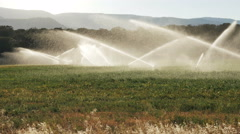 Morning sun lights sprinklers in mountain field cedar hills mountains background - stock footage