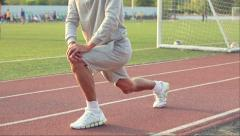 Young athlete doing a warm up leg stretch before a race. Stock Footage