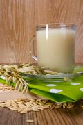 oat decoction in a transparent mug, grains and ears - stock photo