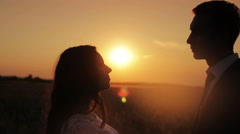 Silhouette of a young beautiful couple bride and groom at sunset gently kissing Stock Footage