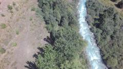 Flying backwards above mountain river and trees Stock Footage