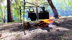 Cooking over a campfire in the woods Stock Footage