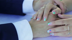 Hands of bride and groom close-up on the table gently stroking the hand of a Stock Footage
