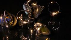 Various pieces of jewelry fall on black reflective surface, super slow motion. Stock Footage