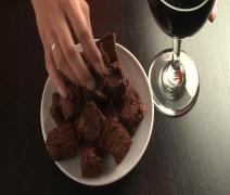Young Female Hand Reaches for Brownies and Red Wine, mixed ethnicity Stock Footage
