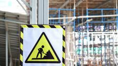 Video A caution construction danger sign in front of blur building site Stock Footage