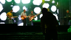 Guy spectator in front of concert stage hold bottle of beer Stock Footage