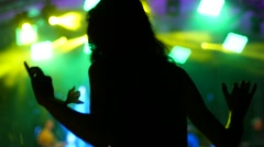 Young spectator girl fan cheerfuly dancing on a concert flash light lumiere Stock Footage