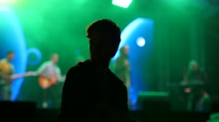 Audience guy entertain public in front of stage on music concert with rope ball Stock Footage