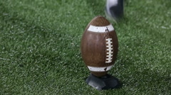 A kicker kicks a football off of a tee - stock footage