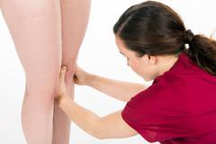 physiotherapist doing knee evaluation - stock photo