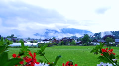 Houses village in Switzerland with red flower foreground and mountain background Stock Footage