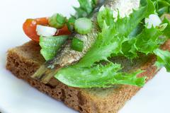 sprats on the bread - stock photo