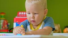 Stock Video Footage of Toddler boy practice to paint with crayons