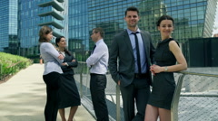Businesscouple smiling to the camera next to their colleagues, steadycam shot Stock Footage