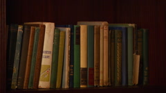 Various books arranged in bookshelf - stock footage
