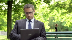 Businessman compare data on laptop and smartphone, steadycam shot Stock Footage