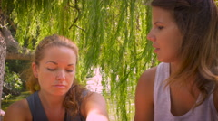 Two young girlfriends have serious conversation and hug and console each other Stock Footage