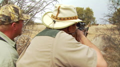 Hunter aiming wildebeest with long rifle - stock footage