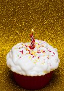 Stock Photo of Cupcake with a lit candle over bright background
