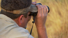 Tourist looking through binoculars at ranch Stock Footage
