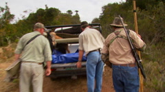 Hunters examining dead animal in trunk of car Stock Footage