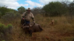 Hunter posing with dead wildebeest - stock footage