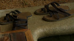 Two pairs footwear kept on poolside - stock footage