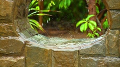 Water dripping from stonewall niche during rainfall Stock Footage