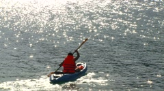 Man kayaking on sea near island Stock Footage