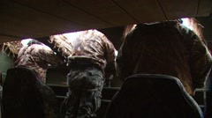 Hunters observing from hunting blind while duck hunting Stock Footage
