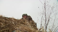 Hunters coming out of hunting blind while duck hunting Stock Footage