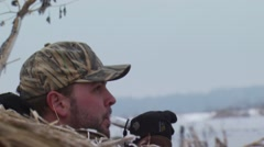 Hunter blowing duck call from hunting blind Stock Footage
