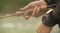 Fly fisher adjusting the string of fishing rod Stock Footage