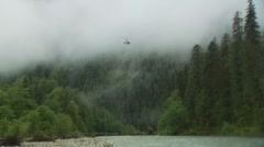 Helicopter landing on river bank in forest Stock Footage